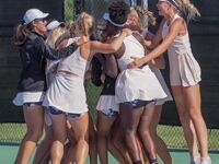 Women's tennis players jump and hug one another on the court.