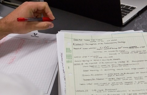 A student takes notes with paper and a laptop.