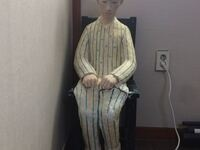 A statue of Hwang Yumi is sitting in a chair in the corner of the room below the window with daylight shining through. After working at a Samsung Electronics semiconductor plant, Hwang Yumi died of acute myeloid leukemia. She is wearing striped hospital pants, a top, a pink cap, and pink socks. She is looking down toward the floor and her two hands are on her thighs in fists. There are two potted plants on the windowsill. Next to the chair is an outlet with a single white plug and cord trailing out of the frame of the image. Statue made by Pak Yujin.