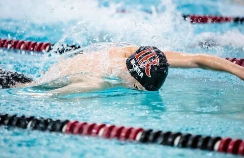 A member of the men's swimming team swims front stroke in the pool.