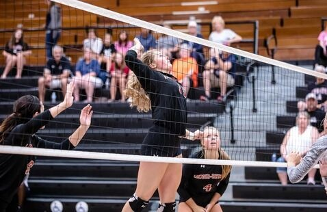 Volleyball player jumps up to spike the ball over the net.