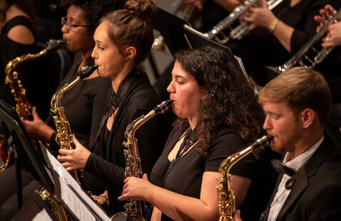 Students in Wind Symphony play on stage during performance