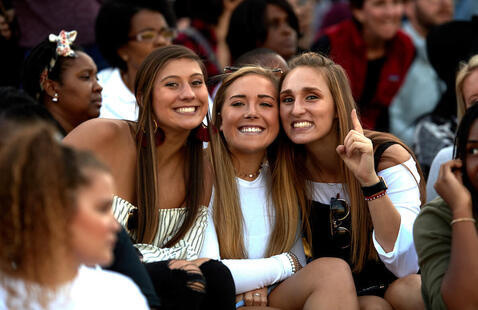 Three smiling students in stands during game