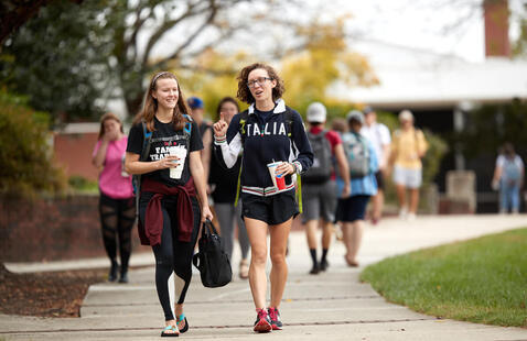 Two female students walking ahead of other students in between classes on campus
