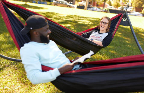 Two students talking while hanging out in hammocks