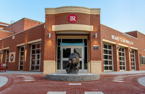 The Bears Club Pavilion entrance with a statue of a black bear placed in front of the doors.