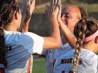 Two Bearkat Women's Soccer players do a double high-five on the field. They are both smiling and happy.