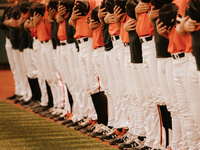 Bearkat Baseball players stand in a perfect line and hold their baseball caps over their hearts as the national anthem plays.