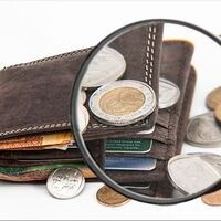 Wallet and coins under a magnifying glass