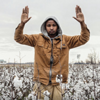 Man standing in a field with his hands up in surrender