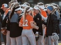 Bearkat Softball players huddle together on the field in their uniforms and jackets.