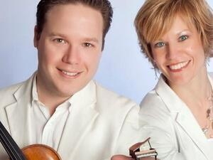 Person holding a violin and another person holding a tiny piano in their hand.