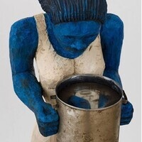 Photo of a small sculpture in the shape of a figure holding a metal pot. The figure is completely blue and wearing a white dress. They are looking down into the pot they are holding. The pot's surface is reflective. In the reflection of the pot, a face is staring back at the figure. The face is blue and white.⠀