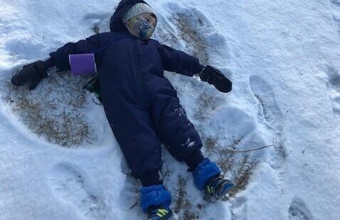 kid making a snow angel