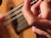 image of hands on a guitar