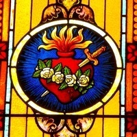 Catholic icon of heart with flames, dagger, and white rose wreath