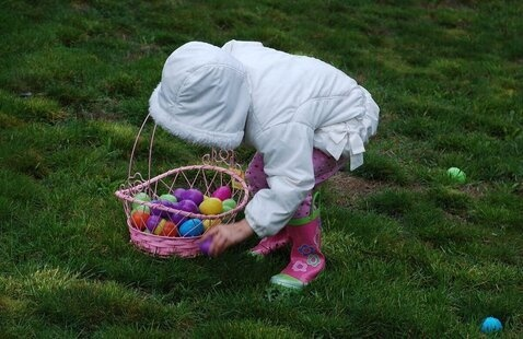 child placing easter eggs in basket