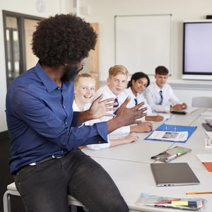 male high school teacher sitting at table