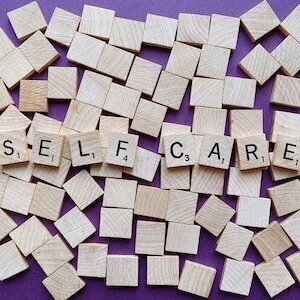 scrabble tiles spell out 'self care'