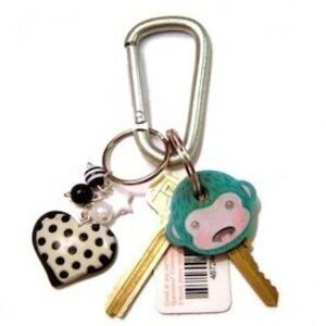 carabiner with monkey and heart keychains and two gold keys