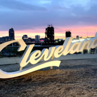 The iconic Cleveland sign overlooks the city skyline at sunset.