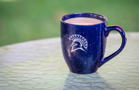 Blue mug with a white Spartan head on a glass table