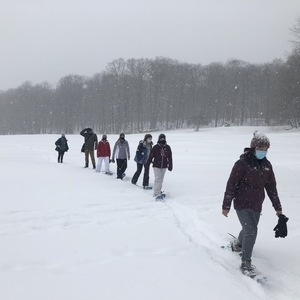 Students snowshoeing while wearing masks