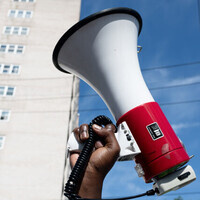 A Black hand holding up a bullhorn against a city backdrop