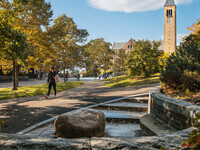 Student walking on Ho Plaza with McGraw Tower in background