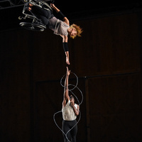 Alice Sheppard, a light-skinned multiracial Black woman with short curly hair, suspends magesticaly from the ceiling; one arm clasped to a cable that hooks onto her wheelchair, and another outstretched straight down towards the floor. Jerron Herman, a medium-height  dark-skinned Black man with a beard and kinky high top black hair, jumps up towards Alice's outstretched hand. He is looking directly up at her and his right and is just shy of meeting hers. His palsied left arm clings to his chest. Silver barbed wire cascades all around Jerron's body, encircling him in a sculptural framework. Photo by Grace Kathryn Landefeld, courtesy Jacob's Pillow.