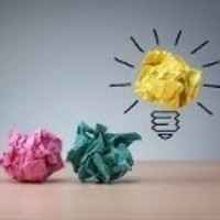 Crumpled colored paper that becomes a lit light bulb