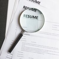 Picture of a magnifying glass on top of 3 resumes.