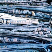 Image is of several pairs of jeans in different washes/colors stacked on top of each other.