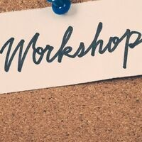 Workshop is written on a strip of paper and pinned to a bulletin board with a blue tack.