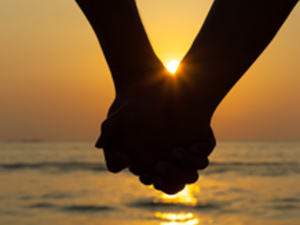 A couple holding hands silhouetted against a setting sun at the beach