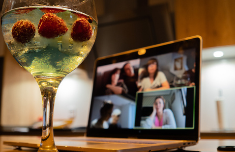 Glass with fruit beverage and a video chat on a laptop