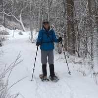 Person snowshoeing along trail