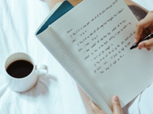 Person writing in a notebook with cup of coffee