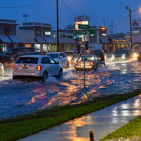 cars drive through flooding