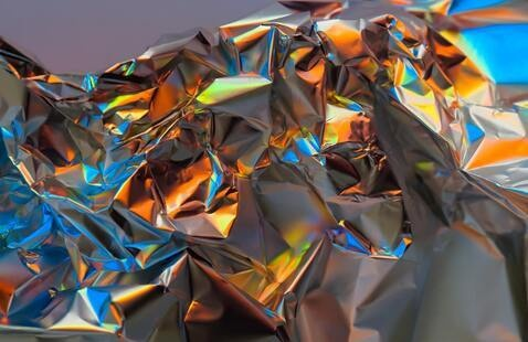 image of crumpled silver metal refracting a spectrum of colors