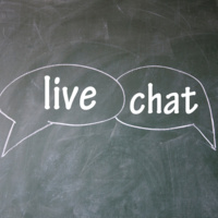 Two chat bubbles drawn on a blackboard. The left chat bubble has the word live inside of it, and the right chat bubble has the word chat in it.