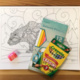 Coloring book page with pencil sharpener, colored pencils, and crayons.