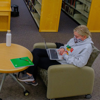 Photo of young woman sitting in chair with computer and mask in front of library stacks.