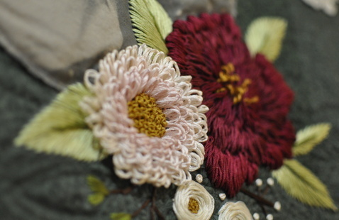 detail of embroidery flowers on a quilt