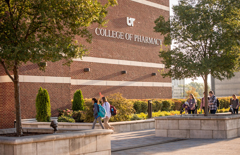 Students walking into the College of Pharmacy building.