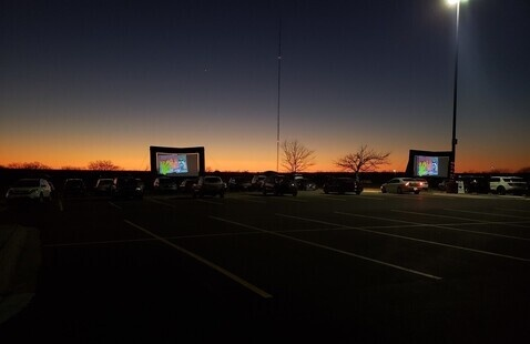 Cars in front of two large screens for a drive in movie