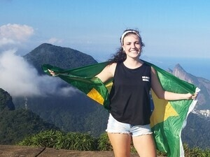 Student in Brazil holding Brazil flag with a mountain in the background