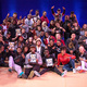 A photo of a group shot of participants in a previous B-Series battle and jam with lots of people smiling and posing including the winners at front holding certificates.