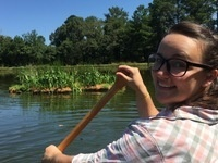 A happy person paddling to a floating wetland.
