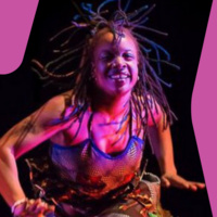 An African-American woman dances with flexed hands, leaning toward the camera, smiling.